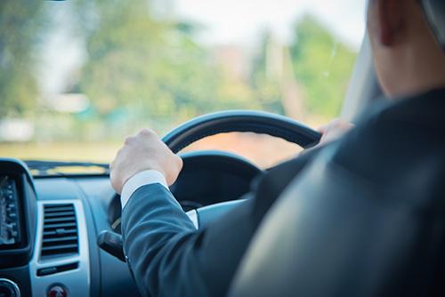 男性ドライバーが自動車のハンドルを握っている